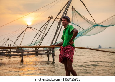 COCHIN, INDIA - MARCH 13, 2012: Unidentified fisherman and chinese fishing nets in Fort Kochi in Cochin, India