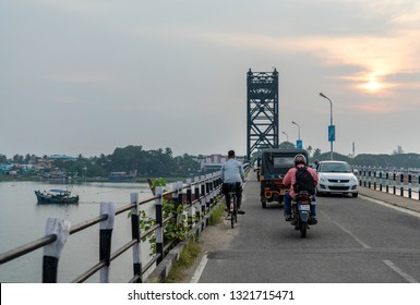 COCHIN, KERALA, INDIA - NOVEMBER 1, 2018: As the sun sets over Willingdon Island, traffic passes over the old Mattancherry Bridge, built in 1940 to connect Cochin (Kochi) with the man-made island.