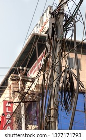 COCHIN, KERALA, INDIA - NOVEMBER 1, 2018:  A utility pole supporting a mass of wiring, some of it haphazard, on a street corner in the Indian town of Cochin (Kochi) in the southern state of Kerala.
