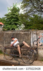 COCHIN, KERALA, INDIA - NOVEMBER 1, 2018: A western tourist reclines on a rickety home-made cart, parked on the pavement of a street, in the town of Cochin (Kochi), in the southern state of Kerala.