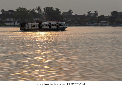 COCHIN, KERALA, INDIA - NOVEMBER 1, 2018: As the sun sets over the Indian state of Kerala, a Cochin ferry sails into the reflected light, heading for the Fort Kochi Ferry Station on the mainland.