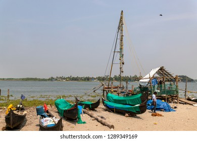 COCHIN, KERALA, INDIA - OCTOBER 31, 2018: Cochin beach, where the Indian shore is lapped by the Arabian Sea, with small fishing boats and a solitary Chinese fishing net, for which the area is famous.