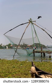 COCHIN, KERALA, INDIA - OCTOBER 31, 2018: A Chinese fishing net is raised, aided by rocks as counterbalance, is this popular tourist area of Cochin (Kochi), a city in Kerala alongside the Arabian Sea.