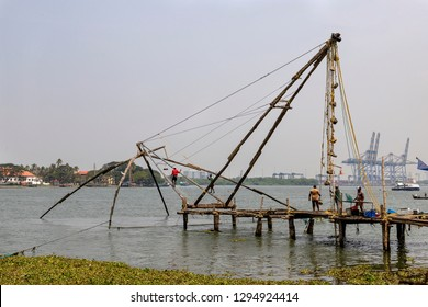 COCHIN, KERALA, INDIA - OCTOBER 31, 2018: Fishermen raise their Chinese fishing net at Cochin in Kerala.  These renowned nets are briefly lowered, before lifting small quantities of fish afterwards.