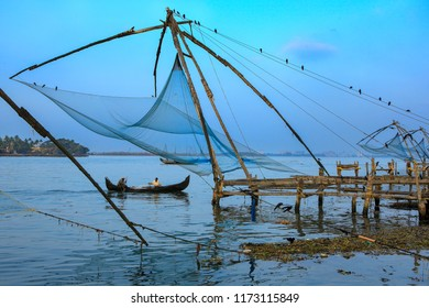 Cochin,December,17,2008:local unidentified fishermen fishing in small boat near chinese fishing nets, famous tourist spot against harbour  background,fort Cochin,Kerala,India, Asia