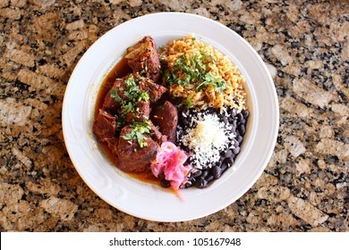 Cochinita pibil plate, Achiote roasted marinated pork shoulder served with habanero onions, beans, and rice.