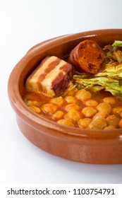 Cocido de Madrid, traditional Spanish dish with chickpeas. meat, sasuages, and vegetables, in a typical dish, isolated on white