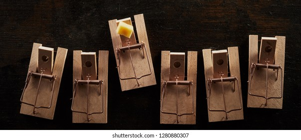 Cocked mousetrap with cheese standing out of other wooden spring-loaded empty traps. Top view on dark background