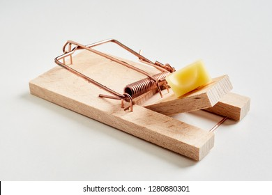 Cocked wooden spring mousetrap with cheese bait, sitting on white surface and viewed in close-up