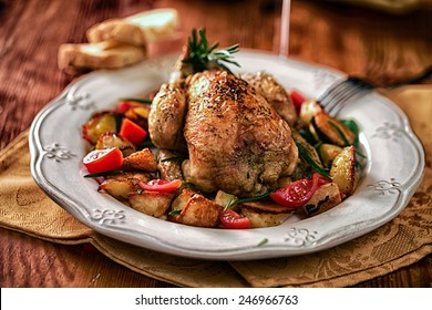 Cockerel baked with potatoes and tomatoes