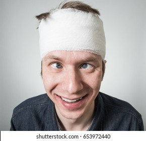 Cockeyed young guy with bandage on his head. Image related with treatment of the wounds