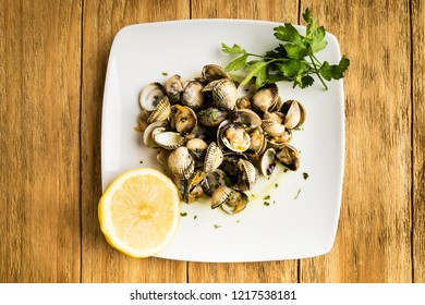 cockles cooked with parsley and half a lemon on a white plate on a wooden table
