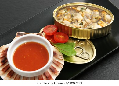 Cockles served inside the can with tomato sauce over scallop shell.