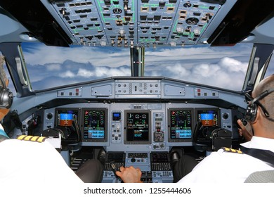 Cockpit of civil airliner flying on a high altitude above the clouds.