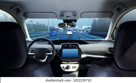 Cockpit of driverless car driving on highway viewed from rear seat.