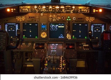 Cockpit (flight deck) of a modern commercial passenger jet aircraft showing the control columns (yoke) with instruments in the background. Glass cockpit. Aviation concept.
