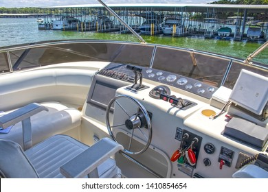 Cockpit of luxury cabin cruiser out on lake nearing marina - no one sitting in captains seat