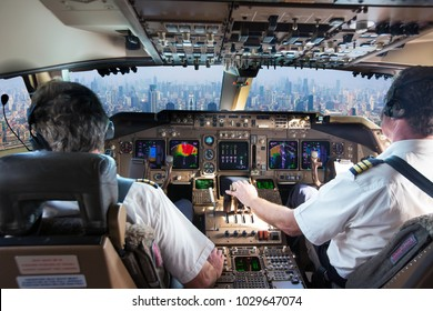 The cockpit of a modern passenger aircraft in flight. Pilots at work. A view from the cockpit to the skyscrapers of the business center of a big city.