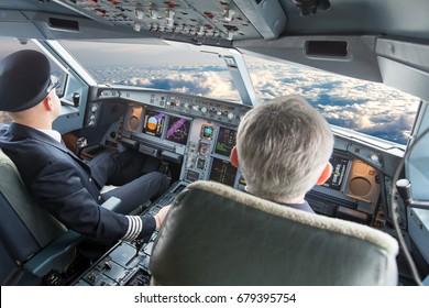 Cockpit of modern passenger aircraft in flight. Pilots at work.