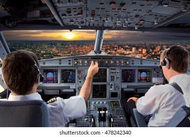 Cockpit view of modern airplane in flight during the sunset. Aircraft pilot at work.