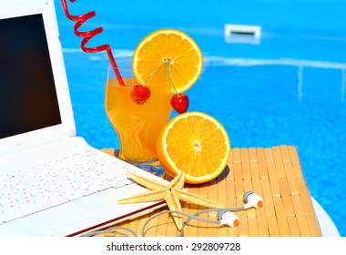 Cocktai with fruits, laptop and starfish on pool background