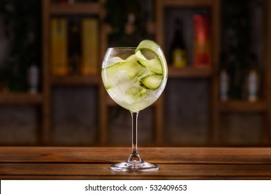 Cocktail with alcohol, cucumber slices, herbs and ice cubes on a wooden table with blurred background of bottles and light.