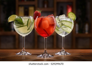 Cocktail with alcohol, lime slices, strawberries, cucumbers and ice cubes on a wooden table with blurred background of bottles and light.