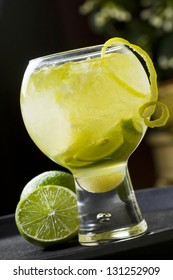 Cocktail with alcohol and limes over black background