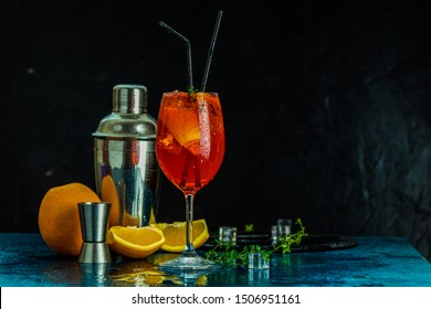 Cocktail aperol spritz in big wine glass with water drops on dark background. Summer alcohol cocktail with orange slices. Italian cocktail aperol spritz on slate board. Trendy beverage