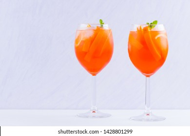Cocktail Aperol Spritz with mint leaves on a white background. Italian cocktail aperol spritz on white background