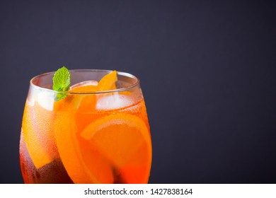 Cocktail aperol spritz on black background. Summer alcohol cocktail with orange fruit and fresh mint. Italian cocktail aperol spritz on wooden boards