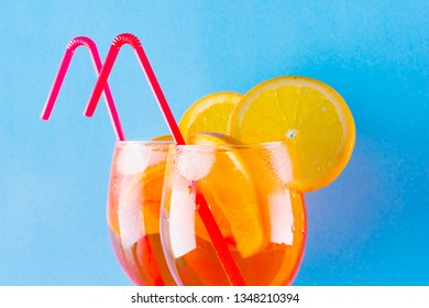 Cocktail aperol spritz on blue background. Summer alcoholic cocktail with orange slices. Aperol spritz on colored background. Coral colored cocktail in minimalism style