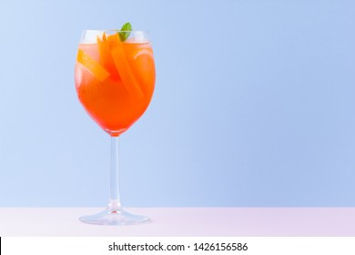 Cocktail Aperol Spritz on a blue pink background. Italian cocktail aperol spritz in pop art style. Summer trendy drink on pastel background