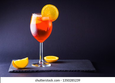 Cocktail aperol spritz on dark background. Summer alcohol cocktail with orange slices. Italian cocktail aperol spritz on slate board. Trendy beverage