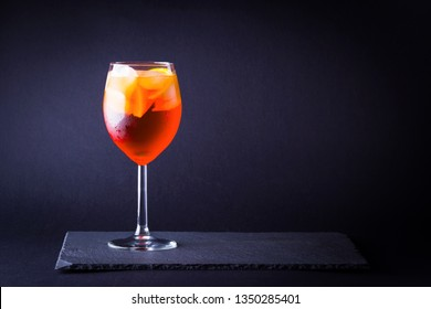 Cocktail aperol spritz on dark background. Summer alcohol cocktail with orange fruit in minimalism style. Italian cocktail aperol spritz on slate board