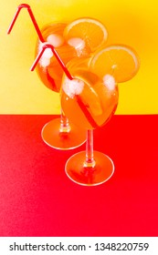 Cocktail aperol spritz on red yellow background. Summer alcoholic cocktail with orange slices. Aperol spritz on colored background. Coral colored cocktail in minimalism style