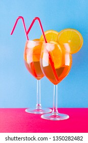 Cocktail aperol spritz on red blue background. Summer alcoholic cocktail with orange slices. Aperol spritz on colored background. Coral colored cocktail in minimalism style
