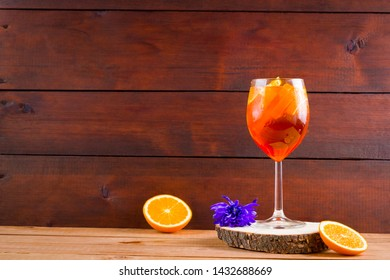 Cocktail aperol spritz on wooden boards. Summer alcoholic cocktail with orange slices and flowers. Aperol spritz on wooden boards