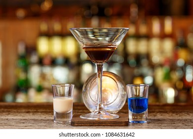 A cocktail based on sambuca and liqueurs stands on a wooden counter in a night club or in a pub. The ingredients of the drink - sambuca and liqueurs - are in different glasses.