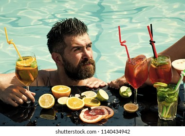 Cocktail and bearded man in pool. Drink, food and relax. Leg of girl and guy with alcoholic beverage and fruit. Man swimming in water pool. Summer vacation and party.