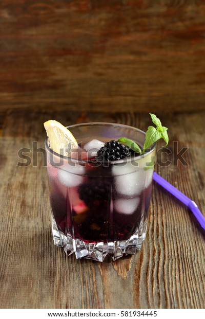 Cocktail with blackberry, lemon and mint, vertical