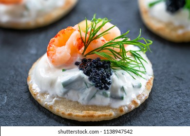 Cocktail blinis with crayfish, caviar and sour cream - gourmet party food.