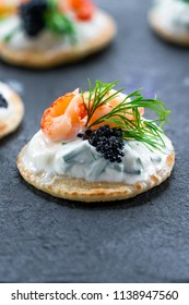 Cocktail blinis with crayfish, caviar and sour cream - gourmet party food idea