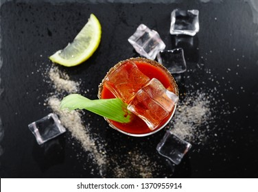 Cocktail Bloody Mary in a glass on a black stone background, top view, a cocktail of vodka and tomato juice with celery, lemon and spices