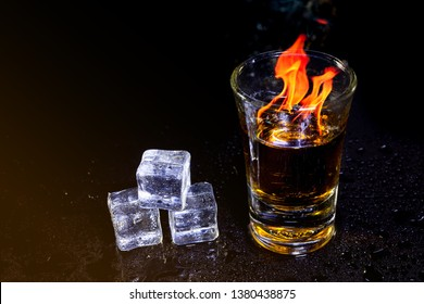 Cocktail blue burning in shot glass  with salt and lime, ice cubes on black background.