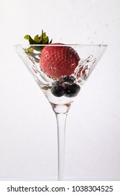 cocktail of blueberries and strawberries splashing