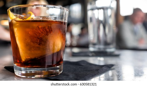 Cocktail close up. Bar or restaurant with blurred people in the background.
