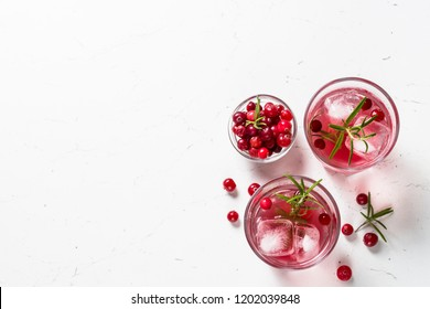 Cocktail with cranberry, vodka, rosemary and ice. Top view on white.