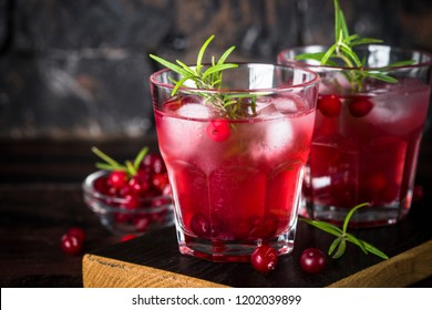 Cocktail with cranberry, vodka, rosemary and ice on dark.