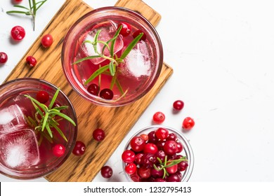 Cocktail with cranberry, vodka, rosemary and ice. Top view with copy space on white table.